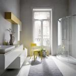 Une douche italienne très moderne qui s'impose dans l'espace tout en fluidité. L'idée déco de l'architectes interieur paris: Cette pièce longitudinale a été transformée avec une douche en ellipse qui casse la forme d'origine «à couloir». Des rangements superposés donnent du dynamisme à l'aménagement linéaire de la salle de bain sur mesure paris